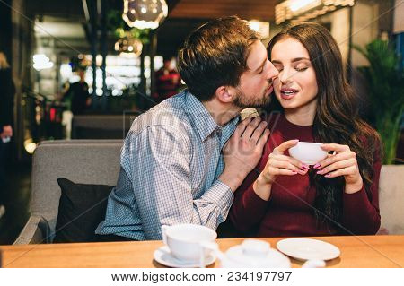 Attractive Man Is Sitting With His Girlfrien At The Table And Kissing Her. She Is Holding A Cup Of T