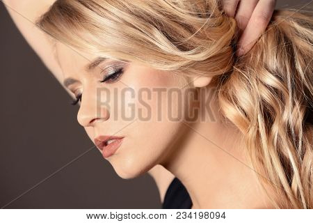 Beautiful young woman with long wavy hair on color background, closeup