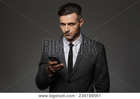 Image of serious man employer dressed in business costume using cell phone in office isolated over gray background