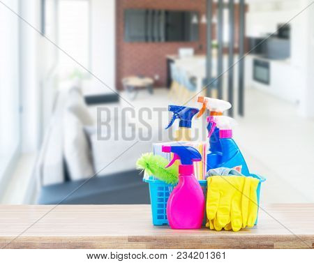Spring Cleaning Concept - Colorful Spays And Rubbers On Wooden Table In Open Space Apartment