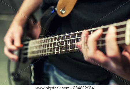 Hands The Bass Player. Closeup. Playing The Guitar. Selective Focus.