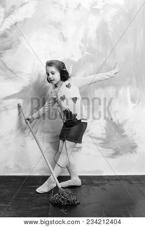Small Girl Listen Music With Mop. Child Cleaner With Broom On Colorful Background. Cleanup And Order