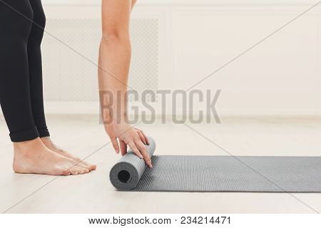 Pilates Background. Unrecognizable Woman Rolling Up Yoga Mat After Training. Sport Class Before Or A