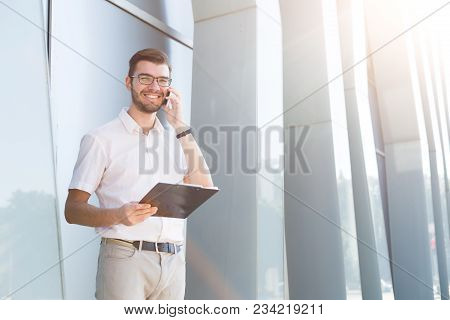 Attractive Happy Businessman In Eyeglasses Is Holding Clipboard And Talking On Mobile Phone While St