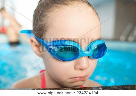 Close-up Of Sad Little Girl Wearing Swimming Goggles Sitting In Water And Trying To Not Crying