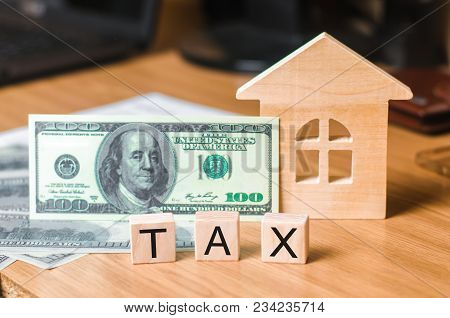 Wooden House And A Bill Of One Hundred Dollars, Inscription Taxes. Concept Of Property Taxes, Purcha