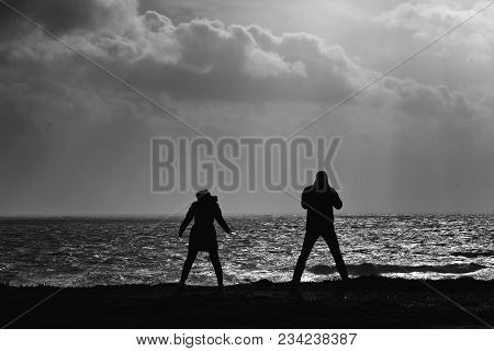 Black And White Image Of Two Young People Standing On The Grass On The Cliffs Edge By The Beach On A