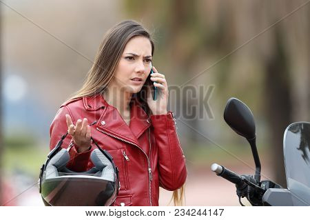 Angry Biker On Her Motorbike Calling Insurance On Phone On The Street