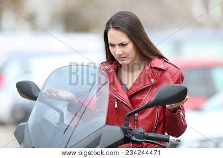 Portrait Of A Confused Biker Looking At Broken Down Motorbike On The Street