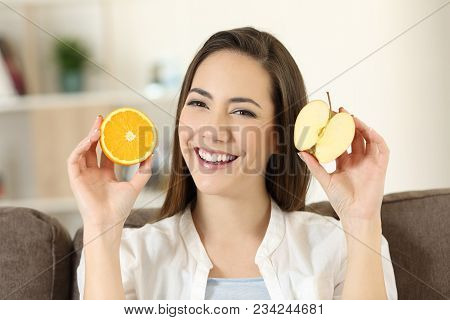 Front View Of A Happy Woman Showing Half Apple And Half Orange Sitting On A Couch In The Living Room