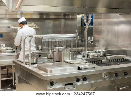 Chef Preparing Food In Commercial Stainless Steel Kitchen In Restaurant