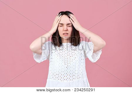 A Young Attractive Brunette Woman Holds Her Head Because Of A Strong Headache And Migraine. Frustrat