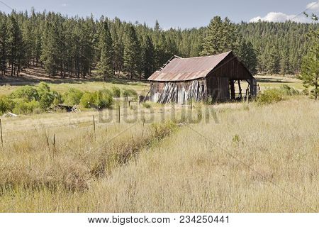 An Old Pioneer Barn With A Rusting Metal Roof In A Grassy Meadow On An Oregon Ranch Is Gradually Fal