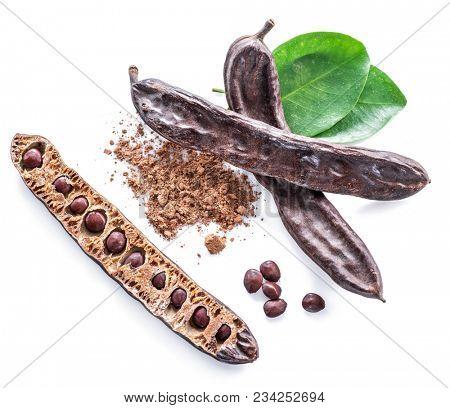 Carob pods and carob powder on the white background. Organic food.