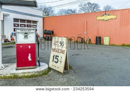 Old Car Repair Shop With A Gas Station, Advertising For Cheap Gasoline, Car Tires, Metal Barrels