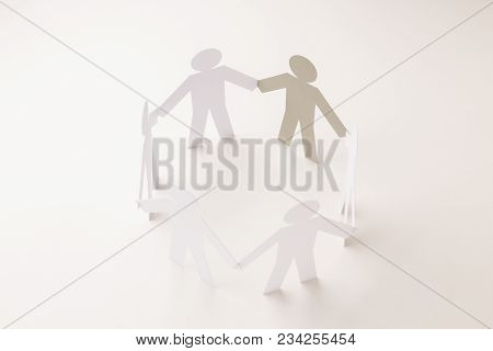 Closed Joining Of Six Paper Figure With Gray One In Hand Down Posture On Bright White Background. In