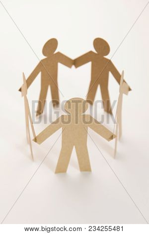 Close Up Of Closed Joining Of Five Brown Paper Figure In Hand Down Posture On White Background. In C