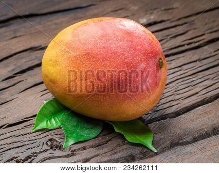 Ripe mango fruit with mango leaves on wooden background. Organic food.