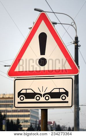 High Risk Of Collision. A Road Sign With An Exclamation Point And Two Cars That Crashed Into Each Ot
