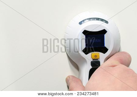 Man Using Stud Finder To Locate Framing Studs Located Behind The Walling Surface. Space For Text.