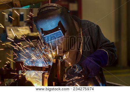 Worker Is Welding Automotive Part In Car Factory