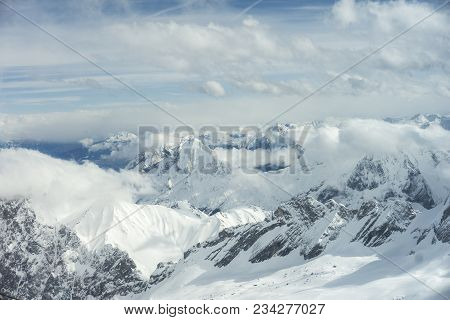 Close-up Of Amazing Snowy Mountains Surrounded By White Clouds In The Bavarian Alps. View To Beautif