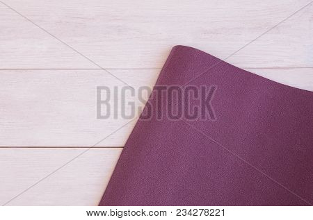 Yoga Accessories, Open  Exercise Mat On White Wooden Background With Copy Space. Concept For Ashtang