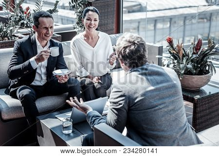 Business Lunch. Smart Nice Delighted Businesspeople Sitting In The Cafe And Talking To Each Other Wh