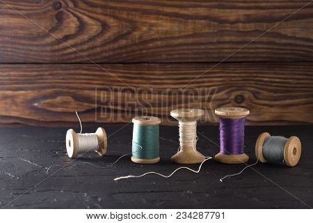 Sewing Thread On Coils, Fabric, Needles For Sewing On Wooden Background. Set For Tailoring Products,