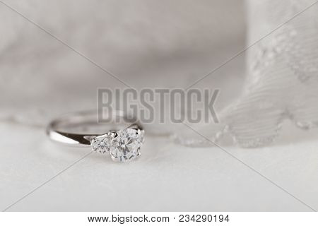 White Gold Wedding Ring With Diamonds On White Background With Lace. Silver Engagement Ring. Nuptial