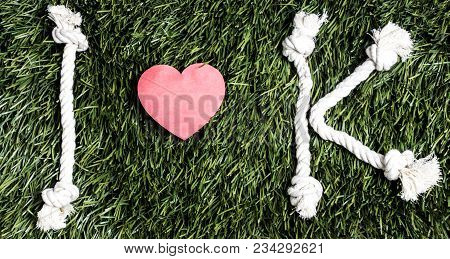 I And K Letters And Three Paper Heart Cut Outs On Grass