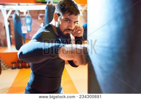 Waist Up Portrait Of Fierce Middle-eastern Fighter Hitting Punching Bag At Boxing Practice In Martia
