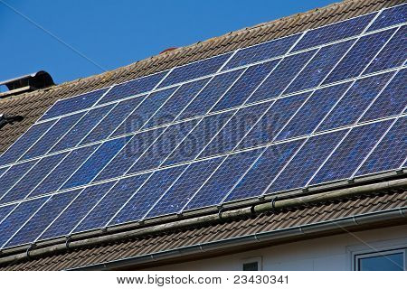Solar cells on a roof in front of a clear blue sky poster