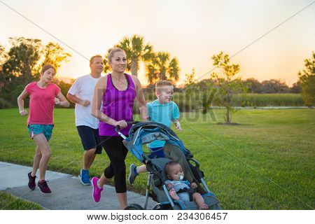 Beautiful, fit young family  jogging together outdoors along a paved sidewalk in a park pushing a stroller at sunset