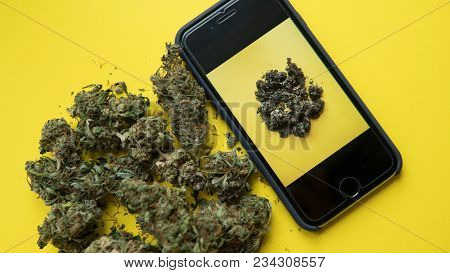 Phone With A Photograph Of Marijuana Lying On A Yellow Background. Social Actions To Support The Leg