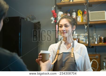 Happy Young Woman Or Waiter Giving Paper Cups With Hot Drinks To Customer At Coffee Shop. Takeaway A