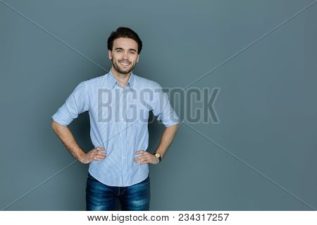 Good Mood. Handsome Nice Stylish Man Smiling And Looking At You While Standing Against The Gray Back