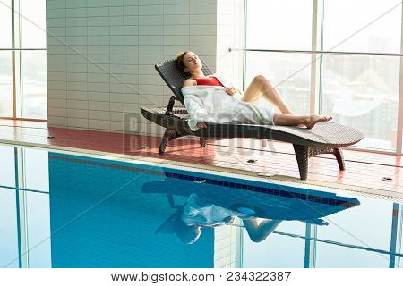 Full Length Portrait Of Beautiful Young Woman Relaxing Lying In Wicker Lounge Chair By Swimming Pool