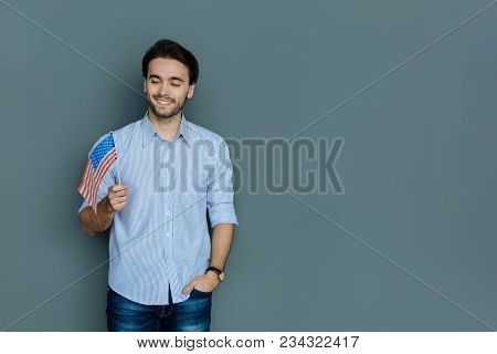 Us Citizen. Handsome Cheerful Young Man Smiling And Looking At The Us Flag While Feeling Patriotic