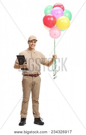 Full length portrait of a delivery man with a clipboard and balloons isolated on white background