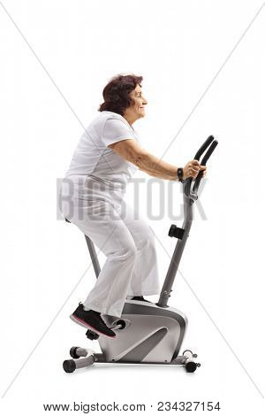 Elderly woman working out on a stationary bike isolated on white background