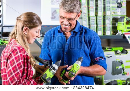 Clerk in electric goods department of hardware store shows several cordless screwdrivers to customer poster