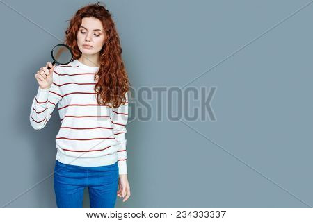 Scientific Research. Nice Serious Young Woman Holding Magnifying Glass And Looking At It While Doing