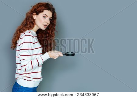 Scientific Lab. Smart Nice Young Woman Looking At You And Using Magnifying Glass While Working In Th