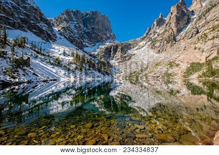 Emerald Lake and reflection with rocks and mountains in snow around at autumn. Rocky Mountain National Park in Colorado, USA.