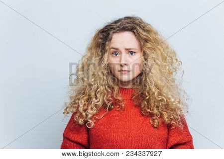 Photo of displeased unhappy young woman with curly bushy blonde hair, frowns face in bewilderment, wears casual clothing, models against white studio background. People and disappointment concept poster