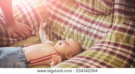 Baby Boy In Jeans With Suspenders Lie In Armchair. Infant Smile To Father. Fathers Day Concept. Happ