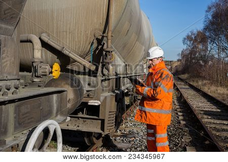 A Railway Worker In High Visibility Clothing Inspecting A Railroad Wagon During A Scheduled Maintena