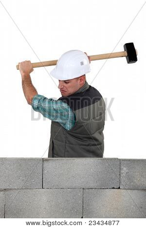 Man hitting a wall with a sledgehammer