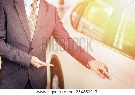 Young Chauffeur In Business Suit Welcoming Rich And Wealthy Client On Board - Rich Lifestyle Taxi Ca